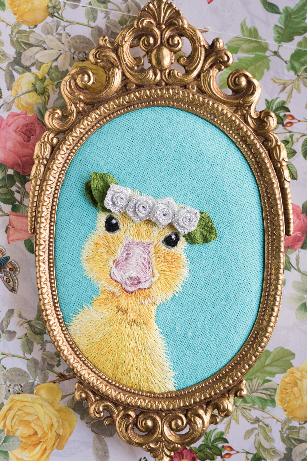 Embroidered duckling in gold ornate oval frame