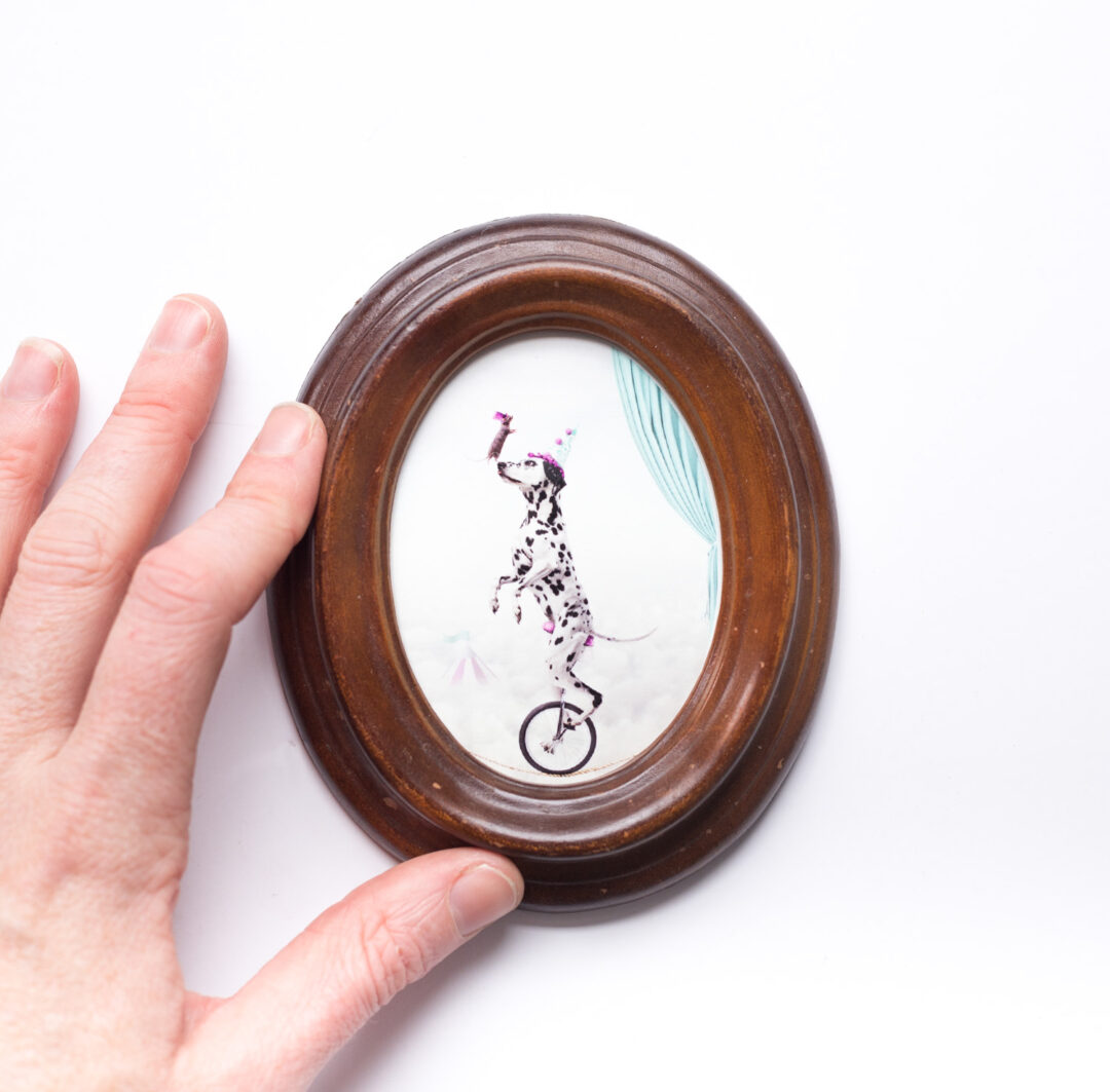 dog on unicycle art print in small oval frame